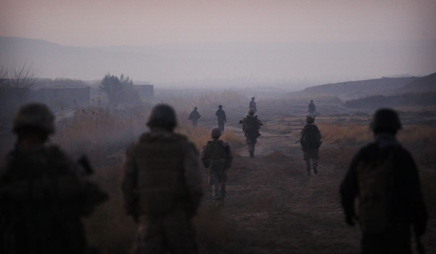 """In this Dec. 23, 2009, file photo United States Marines from the 2nd Battalion 2nd Marines """"Warlords"""" and Afghan National Army soldiers walk in formation during an operation in the Garmsir district of the volatile Helmand province, southern Afghanistan. (AP Photo/Kevin Frayer, File)"""