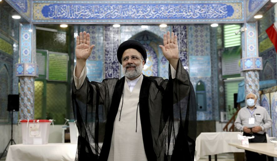 """In this Friday, June 18, 2021, photo, Ebrahim Raisi, a candidate in Iran's presidential elections waves to the media after casting his vote at a polling station in Tehran, Iran. The Biden administration is lashing out at Iran for accusing it of delaying a proposed prisoner swap to force a quick resumption of paused indirect nuclear talks. The State Department on Saturday, July 17, 2021 slammed as """"outrageous"""" comments made by Iran's deputy foreign minister who blamed the U.S. and Britain for the delay. A sixth round of nuclear talks ended last month without agreement ahead of Iran's presidential election won by Ebrahim Raisi. (AP Photo/Ebrahim Noroozi) **FILE**"""