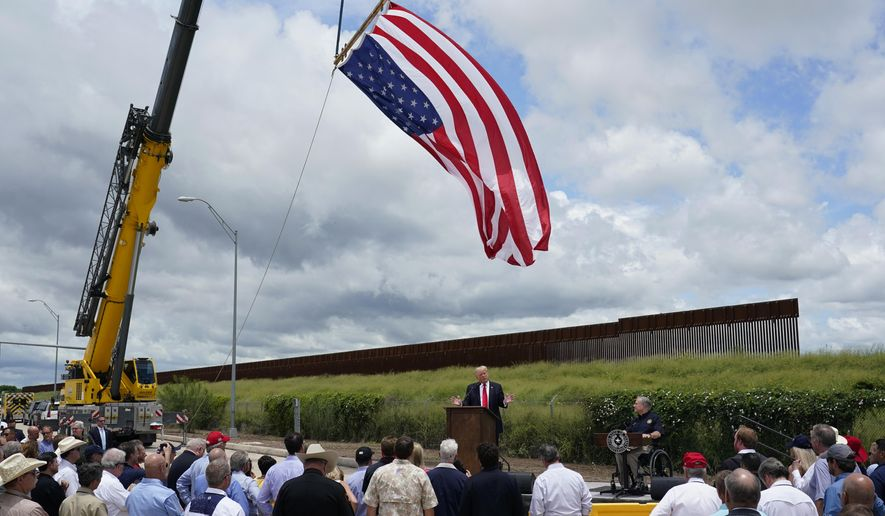 Former President Donald Trump, left, and Texas Gov. Greg Abbott, right, speak during a stop at an unfinished section of border wall, in Pharr, Texas, Wednesday, June 30, 2021. (AP Photo/Eric Gay) **FILE**