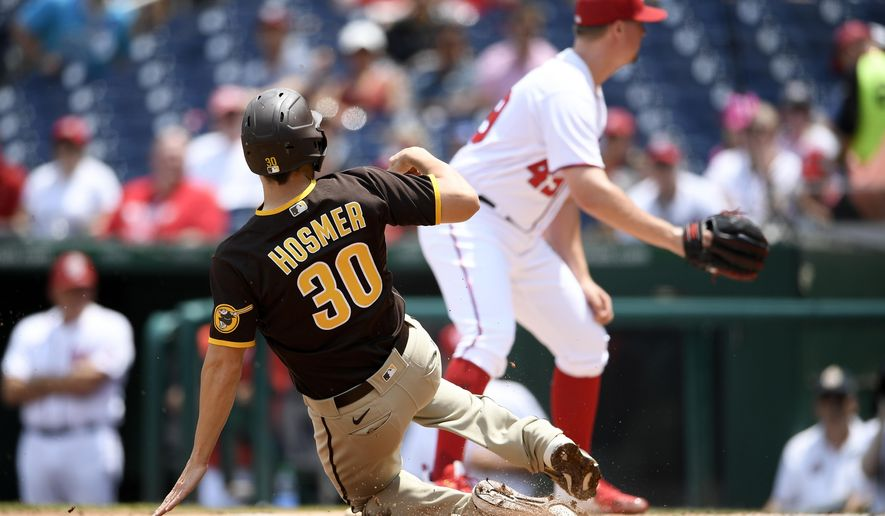 San Diego Padres' Eric Hosmer (30) starts his slide toward home to score on a single by Tommy Pham as Washington Nationals relief pitcher Sam Clay, right, looks for the ball during the seventh inning of the continuation of a suspended baseball game, Sunday, July 18, 2021, in Washington. (AP Photo/Nick Wass)