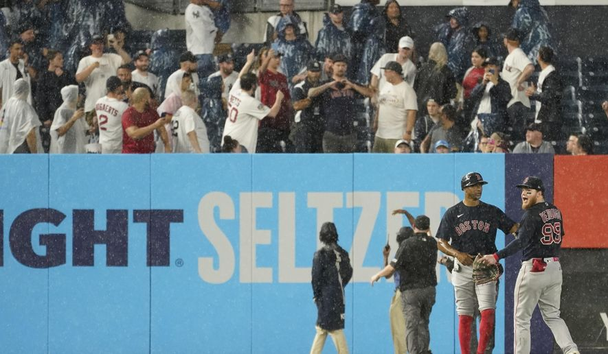 Boston Red Sox first base coach Tom Goodwin, second from left, calms left fielder Alex Verdugo (99) after he was hit in the back by an object thrown by a fan during the sixth inning of a baseball game against the New York Yankees, Saturday, July 17, 2021, in New York. (AP Photo/Mary Altaffer)
