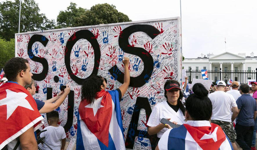 In this file photo, demonstrators write their solidarity with the Cuban people against the communist government, in a rally outside the White House in Washington, Saturday, July 17, 2021. (AP Photo/Jose Luis Magana)
