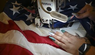 A supervisor sews the stars to finish the assembly of the American flag at North American Manufacturing on June 28, 2021, in Scranton, Pa. Since 2016, the staff at North American Manufacturing on Barring Avenue has meticulously produced about 8,000 full-size American flags each year, which are sold to the Defense Logistics Agency and awarded to government retirees. (Jason Farmer/The Times-Tribune via AP) ** FILE **