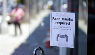 A sign advises shoppers to wear masks outside of a story Monday, July 19, 2021, in the Fairfax district of Los Angeles. Los Angeles County has reinstated an indoor mask mandate due to rising COVID-19 cases. (AP Photo/Marcio Jose Sanchez)