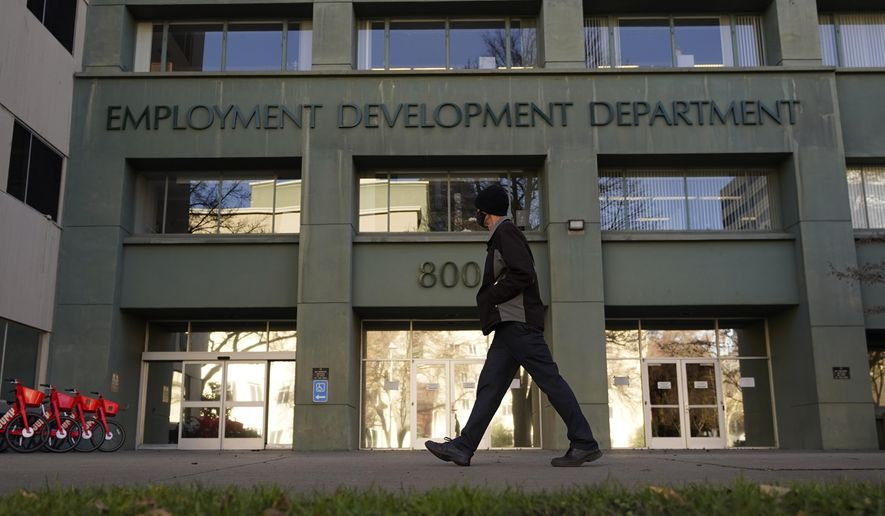 In this Dec. 18, 2020, file photo, a person passes the office of the California Employment Development Department in Sacramento, Calif. (AP Photo/Rich Pedroncelli, File)