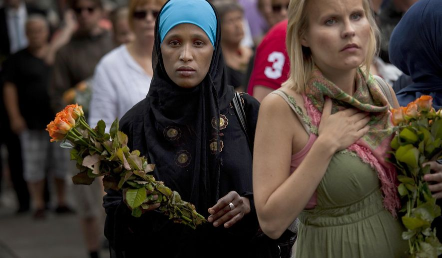 In this Sunday, July 24, 2011, file photo, women carry flowers as they arrive for a memorial service at Oslo Cathedral in the aftermath of the bombing and shooting attacks on Norway's government headquarters and a youth retreat, in Oslo. On the 10-year anniversary of Norway's worst peacetime slaughter, survivors of Anders Breivik's 22 July assault worry that the seam of racism that nurtured the anti-Islamic mass-murderer is re-emerging. Most of Breivik's 77 victims were teen members of the Labor Party Youth wing — idealists enjoying their annual camping trip on the tranquil, wooded island of Utoya. Today many survivors are battling to keep their vision for their country alive. (AP Photo/Emilio Morenatti, File)