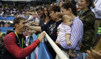 United States' Michael Phelps celebrates winning his gold medal in the men's 200-meter butterfly with his mother Debbie, fiance Nicole Johnson and baby Boomer during the swimming competitions at the 2016 Summer Olympics in Rio de Janeiro, Brazil. (AP Photo/Matt Slocum, File)