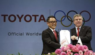 In this March 13, 2015, file photo, Toyota President and CEO Akio Toyoda, left, and IOC President Thomas Bach pose with a signed document during a press conference in Tokyo as Toyota signed on as a worldwide Olympic sponsor in a landmark deal, becoming the first car company to join the IOC's top-tier marketing program. Toyota won't be airing any Olympic-themed advertisements on Japanese TV during the Tokyo Games despite being one of the IOC's top corporate sponsors. The unusual decision by the country's top automaker underlines how polarizing the Games have become in Japan as COVID-19 infections rise ahead of the July 23, 2021, opening ceremony. (AP Photo/Eugene Hoshiko, File)