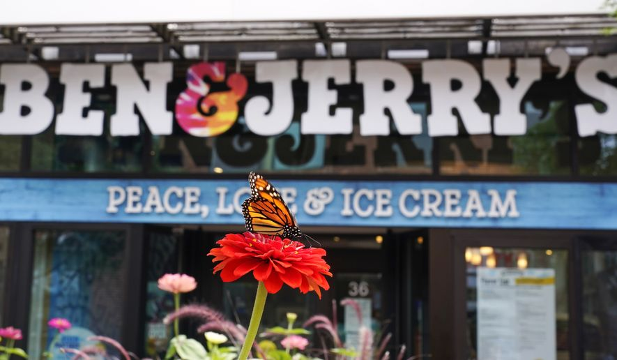 """A Monarch butterfly lands on a flower outside the Ben & Jerry's Ice Cream shop, Tuesday, July 20, 2021, in Burlington, Vt. Ben & Jerry's said Monday it was going to stop selling its ice cream in the Israeli-occupied West Bank and contested east Jerusalem, saying the sales in the territories sought by the Palestinians are """"inconsistent with our values"""". (AP Photo/Charles Krupa)"""