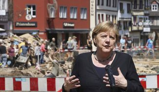 German Chancellor Angela Merkel speaks at a press conference in Muenstereifel, Germany, Tuesday, July 20, 2021. Merkel and North Rhine-Westphalia's Prime Minister Laschet visited Bad Muenstereifel, which was badly affected by the storm. (Oliver Berg/dpa via AP, Pool)