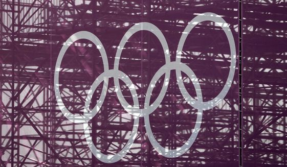 The Olympic rings are set against a lattice work of pipes supporting a grandstand at the skateboarding arena for the 2020 Summer Olympics, Tuesday, July 20, 2021, at the Ariake Urban Sports Park in Tokyo. The pandemic-delayed games open on July 23 without spectators at most venues. (AP Photo/Charlie Riedel)