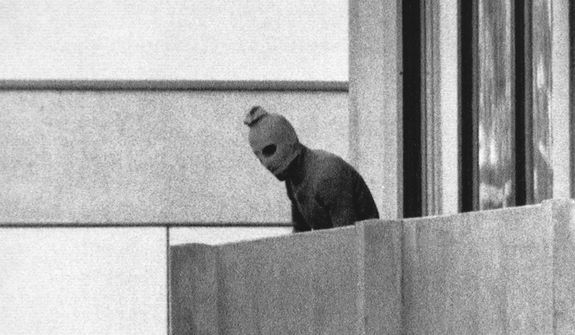 In this Sept. 5, 1972, file photo, a member of the Arab Commando group which seized members of the Israeli Olympic Team at their quarters at the Munich Olympic Village, appears with a hood over his face on the balcony of the village building where the commandos held members of the Israeli team hostage. (AP Photo/Kurt Strumpf, File)  **FILE**