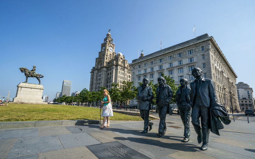 The Beatles statues and Royal Liver Building, center, on the waterfront area of Liverpool, which has been removed from the World Heritage List on Wednesday July 21, 2021.  The UN World Heritage Committee found developments including the new Everton soccer stadium threatened the value of the city's waterfront. (Peter Byrne/PA via AP)