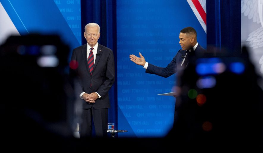 Cameras are visible in the foreground as President Joe Biden accompanied by CNN journalist Don Lemon, right, appears at a CNN town hall at Mount St. Joseph University in Cincinnati, Wednesday, July 21, 2021. (AP Photo/Andrew Harnik)