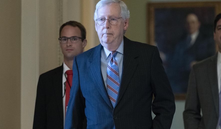 Senate Minority Leader Mitch McConnell, R-Ky., center, walks to his office at the Capitol ahead of a test vote schedule by Democratic Leader Chuck Schumer of New York on the bipartisan infrastructure deal senators brokered with President Joe Biden, in Washington, Wednesday, July 21, 2021. Republicans prepared to block the vote by mounting a filibuster over what they see as a rushed and misguided process. (AP Photo/Jose Luis Magana)