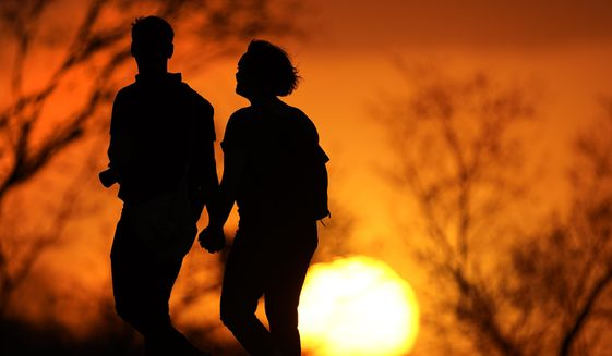 FIn this Wednesday, March 10, 2021, file photo, a couple walks through a park at sunset in Kansas City, Mo. According to a report released by the Centers for Disease Control and Prevention on Tuesday, July 20, 2021, U.S. life expectancy fell by a year and a half in 2020, the largest one-year decline since World War II. Worse, the decrease for both Black Americans and Hispanic Americans was a staggering three years. The decrease is due mainly to the COVID-19 pandemic, which health officials say is responsible for close to 74% of the overall life expectancy decline. (AP Photo/Charlie Riedel, File)