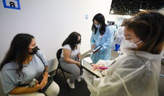 A health care workers register Evelyn Pereira, left, and her daughter Soile Reyes, 12, of Brooklyn, for an appointment for the second dose of the Pfizer COVID-19 vaccine while they wait in the observation area after being vaccinated, Thursday, July 22, 2021, at the American Museum of Natural History in New York. The museum moved their vaccination site from the Hall of Ocean Life where the famous 94-foot-long model of a blue whale is hanging from the ceiling to a smaller adjacent gallery. New York City is closing the big vaccination sites to focus on areas with low vaccination rates. (AP Photo/Mary Altaffer)