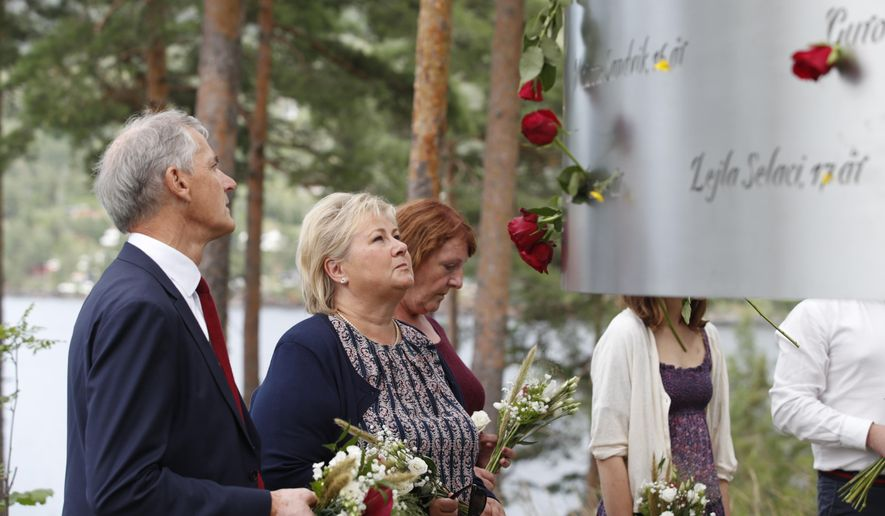 In this July 22, 2019, file photo, Norway's Prime Minister Erna Solberg, center, and leader of the Labour party Jonas Gahr Stoere, left, attend a memorial ceremony to mark the 8th anniversary of the shootings on Utoya Island, where 69 people were killed by Anders Breivik. At 3.25 p.m. on July 22, 2021, a ray of sun should have illuminated the first of 77 bronze columns on a lick of land opposite Utoya island outside Oslo. Over the next 3 hours and 8 minutes, it would have brushed each column in turn, commemorating every person killed by right-wing terrorist Anders Breivik. But on the 10-year anniversary of the terror, the memorial remains a construction site. (Terje Bendiksby/NTB Scanpix via AP, File)