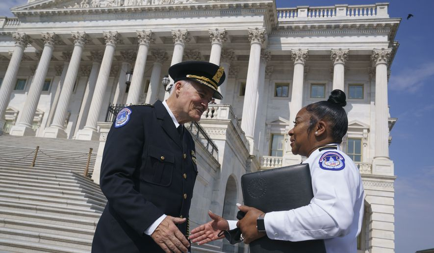 J. Thomas Manger, left, a veteran police chief of departments in the Washington, D.C., region, is welcomed by interim acting U.S. Capitol Police Chief Yogananda Pittman, to the Capitol in Washington, Friday, July 23, 2021, as he takes over the position, following the resignations of the previous leadership after the Jan. 6 insurrection. (AP Photo/J. Scott Applewhite)
