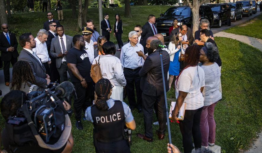 Attorney General Merrick Garland listens to community leaders while visiting a youth baseball game held by the Chicago Westside Sports, a part of The Chicago Police Department's formed Police Athletic League, at Columbus Park in Chicago, Illinois, Thursday, July 22, 2021. Garland is vowing that the Justice Department will crack down on gun trafficking corridors as part of a comprehensive approach to combat surging gun violence. (Samuel Corum/Pool via AP) **FILE**