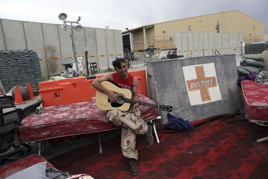 In this July 5, 202, file photo, an Afghan soldier plays a guitar that was left behind after the American military departed Bagram air base, in Parwan province north of Kabul, Afghanistan.  (AP Photo/Rahmat Gul, File)
