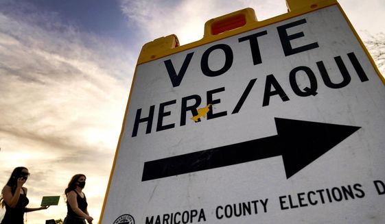 In this Nov. 3, 2020, file photo, voters deliver their ballots to a polling station in Tempe, Ariz. (AP Photo/Matt York)