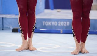 German gymnasts stand with their unitard costumes and wait to perform during the women's artistic gymnastic qualifications at the 2020 Summer Olympics, Sunday, July 25, 2021, in Tokyo. (AP Photo/Ashley Landis)