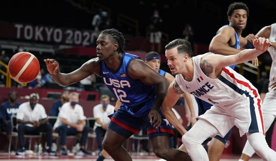 United States' Jrue Holiday, left, fights for a loose ball with France's Thomas Heurtel during a men's basketball preliminary round game at the 2020 Summer Olympics, Sunday, July 25, 2021, in Saitama, Japan. (AP Photo/Charlie Neibergall)