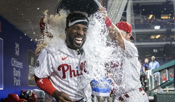 Philadelphia Phillies Andrew McCutchen is doused by  teammates Rhys Hoskins and Archie Bradley after hitting a three-run walkoff home run in the ninth inning of a baseball game against the Washington Nationals, Monday, July 26, 2021, in Philadelphia. (AP Photo/Laurence Kesterson)