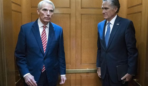 Sen. Rob Portman, R-Ohio, left, accompanied by Sen. Mitt Romney, R-Utah, leave in the elevator after a closed door talks about infrastructure on Capitol Hill in Washington Thursday, July 15, 2021. (AP Photo/Jose Luis Magana)  **FILE**
