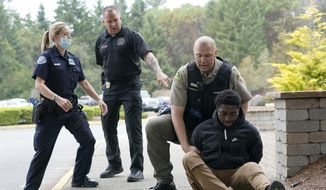 Kevin Burton-Crow, upper-right, of the Thurston Co. Sheriff's Dept., handcuffs Naseem Coaxum, right, an actor playing the role of a person causing a disturbance at a convenience store, during a training class at the Washington state Criminal Justice Training Commission, Wednesday, July 14, 2021, in Burien, Wash., instructor Ken Westphal, second from left, an officer with the Lacey Police Dept., and LeAnne Cone, left, of the Vancouver Police Dept., look on. Washington state is embarking on a massive experiment in police reform and accountability following the racial justice protests that erupted after George Floyd's murder last year, with nearly a dozen new laws that took effect Sunday, July 25 but law enforcement officials remain uncertain about what they require in how officers might respond — or not respond — to certain situations, including active crime scenes and mental health crises. (AP Photo/Ted S. Warren) **FILE**