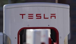 The company logo is shown at the top of a supercharger for Tesla automobiles near shops Feb. 25, 2021, in Boulder, Colo. Tesla's quarterly profit has surpassed $1 billion for the first time thanks to the electric car pioneer's ability to navigate through a pandemic-driven computer chip shortage that has caused major headaches for other automakers. The financial milestone announced Monday, July 26, 2021, extended a two-year run of prosperity that has erased questions about Tesla's long-term viability raised during its early years of losses and production problems. (AP Photo/David Zalubowski, file)