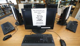 In this Aug. 22, 2019, photo, signs on a bank of computers tell visitors that the machines are not working at the public library in Wilmer, Texas. The Associated Press has learned new details about a ransomware attack that affected roughly two dozen Texas communities two years ago. Thousands of pages obtained by AP and interviews with people involved show Texas communities struggled for days with disruptions to core government services as workers in small cities and towns endured a cascade of frustrations brought on by the sophisticated cyberattack. (AP Photo/Tony Gutierrez) **FILE**