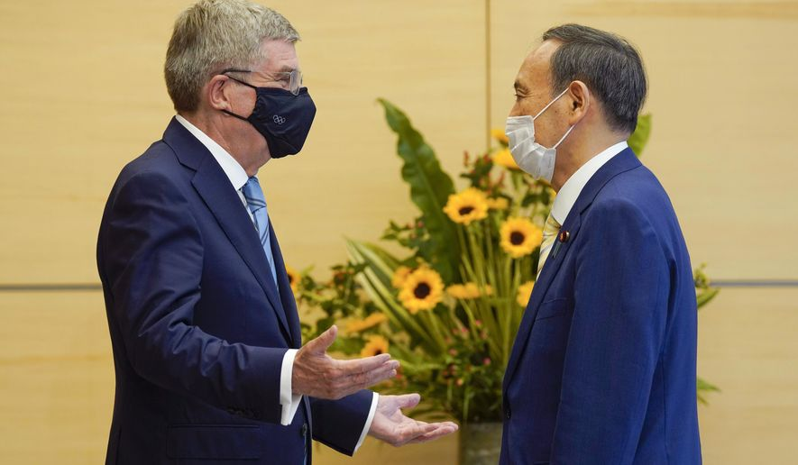 FILE - In this July 14, 2021, file photo, International Olympic Committee President Thomas Bach, left, meets Japanese Prime Minister Yoshihide Suga during his courtesy call at the latter's official residence in Tokyo. How are we to judge the pandemic-delayed Tokyo Olympics when they wrap up in two weeks? It's a straightforward question but it's difficult to answer. That's because there are many interests involved. (Kimimasa Mayama/Pool Photo via AP, File)