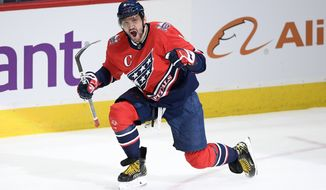 FILE - Washington Capitals left wing Alex Ovechkin celebrates scoring his 718 career goal during the second period of the team's NHL hockey game against the New York Islanders in Washington, in this Tuesday, March 16, 2021, file photo. Ovechkin re-signed with the Washington Capitals on the eve of free agency, Tuesday, July 27, 2021, inking a four-year deal worth $40 million.(AP Photo/Nick Wass, File)