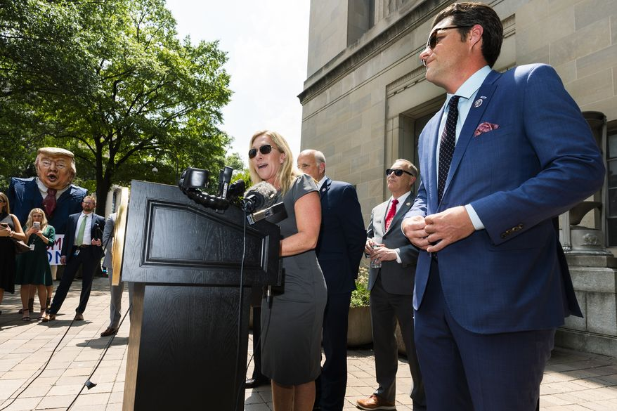"""Rep. Marjorie Taylor Greene, R-Ga., left, together with Rep. Matt Gaetz, R-Fla.,right, and Rep. Louie Gohmert, R-Texas, back center, speaks in front of the Department of Justice building in Washington, during a rally, Tuesday, July 27, 2021, demanding the release of the Jan 6 """"prisoners."""" (AP Photo/Manuel Balce Ceneta)"""