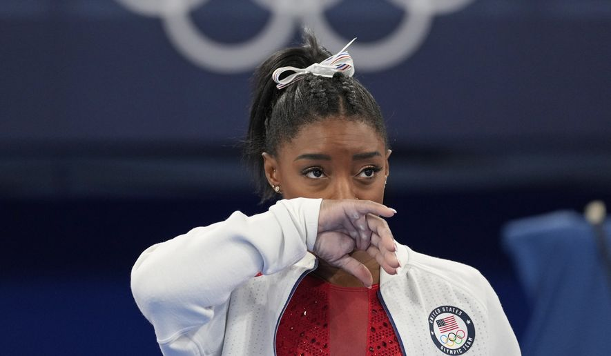Simone Biles, of the United States, watches gymnasts perform after she exited the team final with apparent injury, at the 2020 Summer Olympics, Tuesday, July 27, 2021, in Tokyo. The 24-year-old reigning Olympic gymnastics champion Biles huddled with a trainer after landing her vault. She then exited the competition floor with the team doctor. (AP Photo/Ashley Landis)