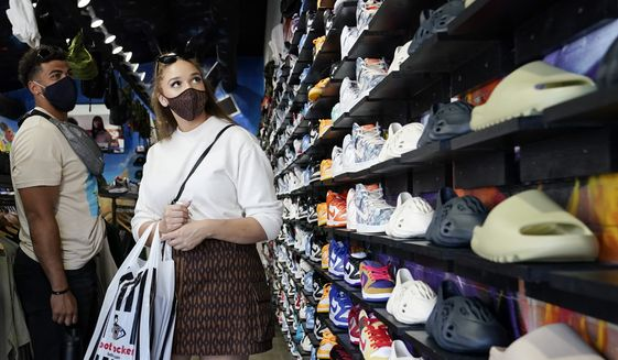 In this Monday, July 19, 2021, photo, shoppers wear masks inside of The Cool store in the Fairfax district of Los Angeles. The Centers for Disease Control and Prevention reversed course Tuesday, July 27, 2021, on some masking guidelines, recommending that even vaccinated people return to wearing masks indoors in parts of the U.S. where the coronavirus is surging. (AP Photo/Marcio Jose Sanchez) **FILE**