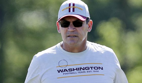 FILE - In this May 15, 2021, file photo, Washington Football Team head coach Ron Rivera watches during an NFL football rookie minicamp at Inova Sports Performance Center in Ashburn, Va. On the eve of the start of training camp, Rivera said Tuesday, July 27, 2021, that over half of his players are now fully vaccinated and expressed frustration about some of the reluctance. (AP Photo/Luis M. Alvarez, File)