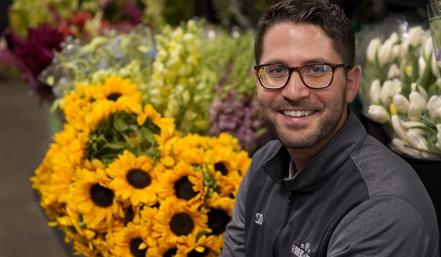 Steven Dyme, owner of Flowers for Dreams, poses for a portrait at his warehouse Friday, July 23, 2021, in Chicago. Dyme says the $15 minimum made it much easier to staff up when the economy reopened this spring and demand for flowers, particularly for weddings, soared. The company has four locations, including its headquarters in Chicago, one in Milwaukee, and two in Detroit. (AP Photo/Charles Rex Arbogast)
