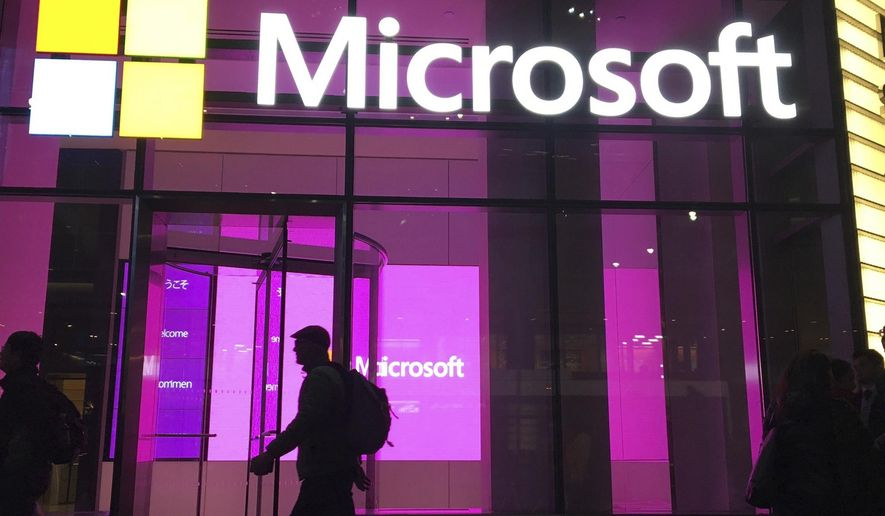In this Nov. 10, 2016, photo, people walk past a Microsoft office in New York. Three tech companies that have amassed unparalleled influence while reshaping the way we live released their latest quarterly report cards in a flurry late Tuesday, July 27, 2021. Although Apple, Microsoft and Google owner Alphabet Inc. make their money in different ways, the results for the April-June period served as another reminder of the clout they wield and why government regulators are growing increasingly concerned about whether they have become too powerful. (AP Photo/Swayne B. Hall) **FILE**