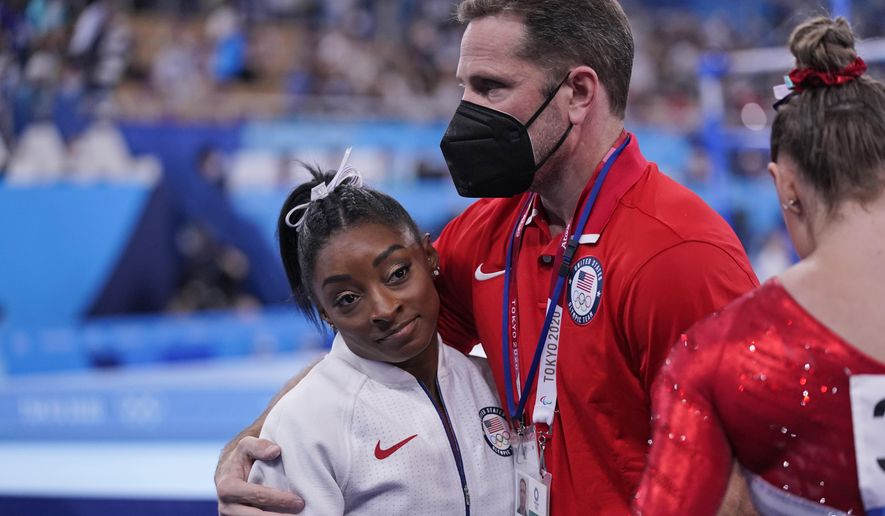 Coach Laurent Landi embraces Simone Biles, after she exited the team final with apparent injury, at the 2020 Summer Olympics, Tuesday, July 27, 2021, in Tokyo. The 24-year-old reigning Olympic gymnastics champion Biles huddled with a trainer after landing her vault. She then exited the competition floor with the team doctor. (AP Photo/Gregory Bull)