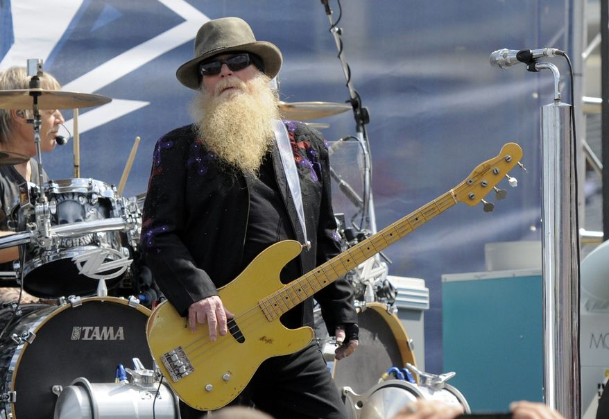 Dusty Hill, of ZZ Top, performs before the start of the NASCAR Sprint Cup series auto race in Concord, N.C., on May 24, 2015. ZZ Top has announced that Hill, one of the Texas blues trio's bearded figures and bassist, has died at his Houston home. He was 72. In a Facebook post, bandmates Billy Gibbons and Frank Beard revealed Wednesday, July 28, 2021, that Hill had died in his sleep. (AP Photo/Mike McCarn, File)