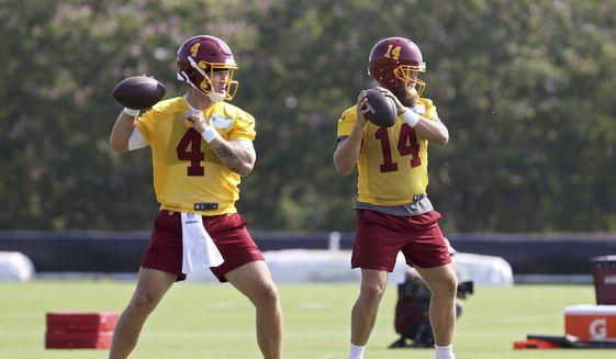 Washington Football Team quarterbacks Taylor Heinicke (4) and Ryan Fitzpatrick (14) throw passes during NFL football practice in Richmond, Va., Wednesday, July 28, 2021. (AP Photo/Ryan M. Kelly) **FILE**