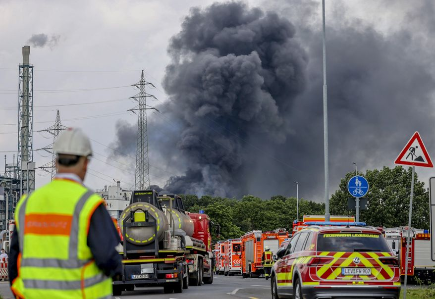 Emergency vehicles of the fire brigade, rescue services and police stand not far from an access road to the Chempark over which a dark cloud of smoke is rising in Leverkusen, Germany, Tuesday, July 27, 2021. After an explosion, fire brigade, rescue services and police are currently in a large-scale operation, the police explained. (Oliver Berg/dpa via AP)