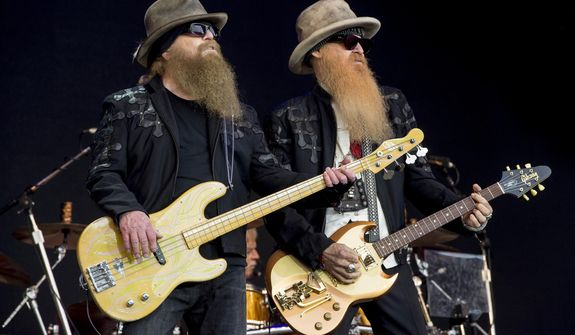 FILE - Dusty Hill, left, and Billy Gibbons from U.S rock band ZZ Top perform at the Glastonbury music festival in Somerset, England, June 24, 2016. ZZ Top has announced that Hill, one of the Texas blues trio's bearded figures and bassist, has died at his Houston home. He was 72. In a Facebook post, bandmates Billy Gibbons and Frank Beard revealed Wednesday, July 29, 2021, that Hill had died in his sleep. (Photo by Jonathan Short/Invision/AP, File)
