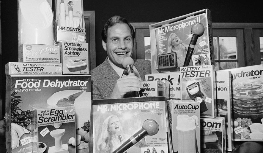 In this Wednesday, Dec. 8, 1982, file photo, Ron Popeil, the man behind those late-night, rapid-fire television commercials that sell everything from the Mr. Microphone to the Pocket Fisherman to the classic Veg-a-Matic, sits surrounded by his wares in his office in Beverly Hills, Calif.  Ron Popeil, the quintessential TV pitchman and inventor known to generations of viewers for hawking products including the Veg-O-Matic, the Chop-O-Matic, Mr. Microphone and the Showtime Rotisserie and BBQ, died Wednesday, July 28, 2021, his family said. (AP Photo/Reed Saxon, File)