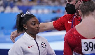 Coach Laurent Landi comforts Simone Biles, of the United States, after she exited the team final with apparent injury, at the 2020 Summer Olympics, Tuesday, July 27, 2021, in Tokyo. The 24-year-old reigning Olympic gymnastics champion Biles huddled with a trainer after landing her vault. She then exited the competition floor with the team doctor. (AP Photo/Gregory Bull)