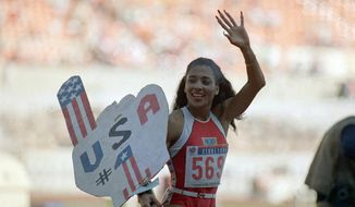 FILE - In this Sept. 29, 1988, file photo, Florence Griffith Joyner, of the United States, waves to spectators as she holds a sign following her world record performance in the finals of the women's 200-meters race, in Seoul, South Korea. The name Flo-Jo is popping up quite a bit these days with sprinters creeping closer to her record times in the women's 100 and 200 races. The late Florence Griffith Joyner has held both marks for three decades. (AP Photo/Lennox McLendon, File)