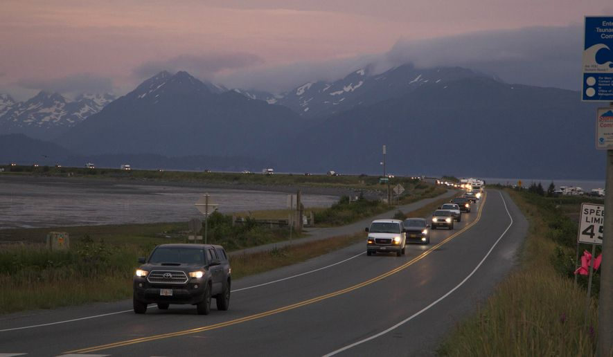 A line of cars evacuates the Homer Spit in Homer, Alaska on July 28, 2021, after a tsunami warning was issued following a magnitude 8.2 earthquake. The tsunami warning for much of Alaska's southern coast was canceled when the biggest wave, of just over a half foot, was recorded in Old Harbor. Alaska. (Sarah Knapp/Homer News via AP)